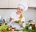 Female cook arranging herbs decoration on plate with salad