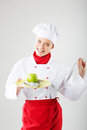Female cook concept dietary chef holding a green apple on a plate with a measuring instrument Royalty Free Stock Image