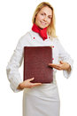 Female cook giving recommendation smiling food with menu in her hand Royalty Free Stock Photo