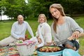 Female cooking meat on portable barbecue group of friends with bbq picnic in park Royalty Free Stock Images