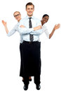 Female corporate waving hi while man stands tall Royalty Free Stock Photo
