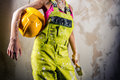 Female in coverall indoors holding paint brush and hardhat over obsolete white background Royalty Free Stock Photos