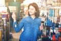 Female customer examining various painting brushes