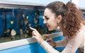 Female customer watching fish in aquarium tank