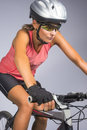 Female cycling athlete riding mountain bike and equipped with pr professional gear isolated over gray vertical shot Stock Photography