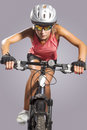 Female cycling athlete riding mountain bike and equipped with pr professional gear isolated over gray vertical shot Royalty Free Stock Photography