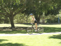 Female cycling through park side view Royalty Free Stock Photography