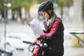 Female cyclist putting package in courier bag young protective gear on street Stock Photo