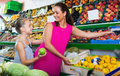 Female with daughter buying fresh apples in fruit section Royalty Free Stock Photo