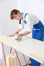 Female decorator pasting wallpaper some Royalty Free Stock Photo
