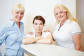 Female dentist with doctors assistant and receptionist standing at the reception Stock Photos
