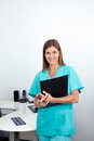 Female dentist holding clipboard in clinic portrait of a happy dental Stock Photography