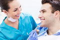 Female dentist with male patient and men in dentist's office Stock Photo