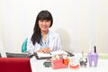 Female dentist young pose form her working desk in dental clinic Royalty Free Stock Image