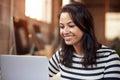 Female Designer Using Laptop At Desk In Modern Office