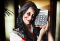 Female devil business woman showing profits concept image of a in terrifying makeup holding a calculator to portraying negetive Royalty Free Stock Photo