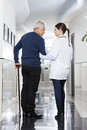 Female doctor assisting man to walk in rehab center rear view of men Stock Photography