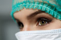 Female doctor face wearing protective mask and green surgeon cap Royalty Free Stock Photo