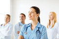 Female doctor in front of medical group attractive or nurse Royalty Free Stock Photos