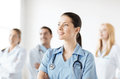 Female doctor in front of medical group attractive or nurse Royalty Free Stock Images