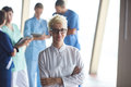 Female doctor with glasses and blonde hairstyle standing in fron Royalty Free Stock Photo