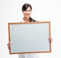 Female doctor holding blank white board smiling young isolated on a background looking at camera Royalty Free Stock Image