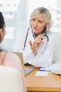 Female doctor listening to patient with concentration at desk in medical office Royalty Free Stock Photography