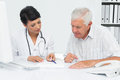 Female doctor with male patient reading reports at medical office Royalty Free Stock Photos