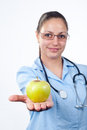 Female doctor offering green apple Royalty Free Stock Photo