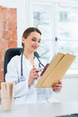 Female doctor reading in document young sitting at a desk front of window clinic a file or dossier Royalty Free Stock Photography