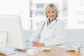 Female doctor sitting with computer at medical office Royalty Free Stock Photography