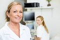 Female doctor smiling with colleague in background portrait of mid adult at clinic Royalty Free Stock Photos