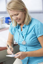 Female doctor in surgery writing out prescription Royalty Free Stock Photos