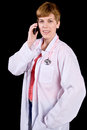 Female doctor talking on a cell phone photographed black background Royalty Free Stock Photos