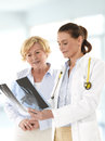 Female doctor talking smiling senior patient showing her x ray image Stock Photography
