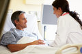 Female doctor talking to male patient in hospital room close up of smiling Stock Photography