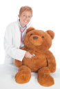 Female doctor with teddy pediatrician or paediatrician a bear making a medical checkup a stethoscope Stock Photography