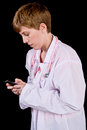 Female doctor texting on a cell phone photographed black background Royalty Free Stock Images