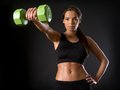 Female doing front shoulder fly photo of a beautiful a with a dumbbell over a dark background Stock Image