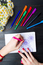 Female drawing flower shapes in notebook Royalty Free Stock Photo