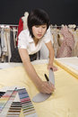 Female dressmaker measuring fabric Royalty Free Stock Photo