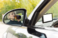 Female driver drinking as she drives reflection in the side view mirror of the car of an alcoholic along the road sipping directly Royalty Free Stock Images