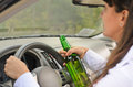 Female driver drinking and driving women while grinning out of the side window as she clutches steering wheel with her bottle of Royalty Free Stock Images