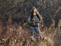 Female duck hunter waterfowl hunting the carry a shotgun and she use a call autumnal bushes on background Stock Photo