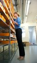Female employee searching through boxes on shelves portrait of a Royalty Free Stock Image