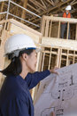 Female Engineer With Blueprint In Construction Site Royalty Free Stock Image