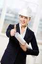 Female engineer with blueprint thumbs up wearing white hand hat Royalty Free Stock Images