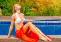 Female enjoying summer holidays woman on day spa relaxation sexy girl sunbathing near pool luxury vacation on tropical resort Royalty Free Stock Photo