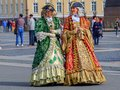 Female entertainers in period dresses awaiting tourists by the Hermitage Winter Palace on Palace Square Saint Petersburg, Russia