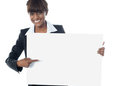 Female executive pointing towards blank banner Stock Photo